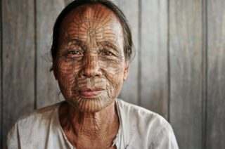 В Мьянме, у жителей племени Чин, существует древняя традиция покрывать лица женщин сплошным узором татуировок.  По легенде, в незапамятные времена бирманский король Алонг Си Тху предпочитал брать в жены красивых девушек из племени чин. Правитель забирал избранниц и навсегда увозил их из родных краёв. Одна смелая девушка по имени Пай сделала татуировку на лице, чтобы «испортить» свою красоту и остаться  на родной земле. Её примеру стали следовать другие девушки племени Чин.  Процесс нанесения татуировок очень болезненный, их делают заостренными бамбуковыми палочками или колючками ротанга без обезболивания. Средний возраст, когда девочкам проделывают эту процедуру, — 10-15 лет.  В 1975 году татуирование лиц запретили, а девочек с татуировками перестали пускать в школу. Но некоторые продолжали совершать процедуру подпольно.  Сейчас молодых бирманок с татуировками почти нет. Участникам Чиптрип-экспедиции «Краски Лой-Кратонга» удалось встретить нескольких представительниц умирающей традиции.  #cheaptripexpedition #чиптрипэкспедиция #племячин #бирма #мьянма
